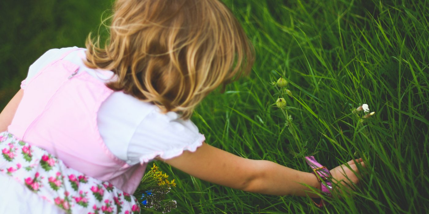 Little girl picking spring flowers