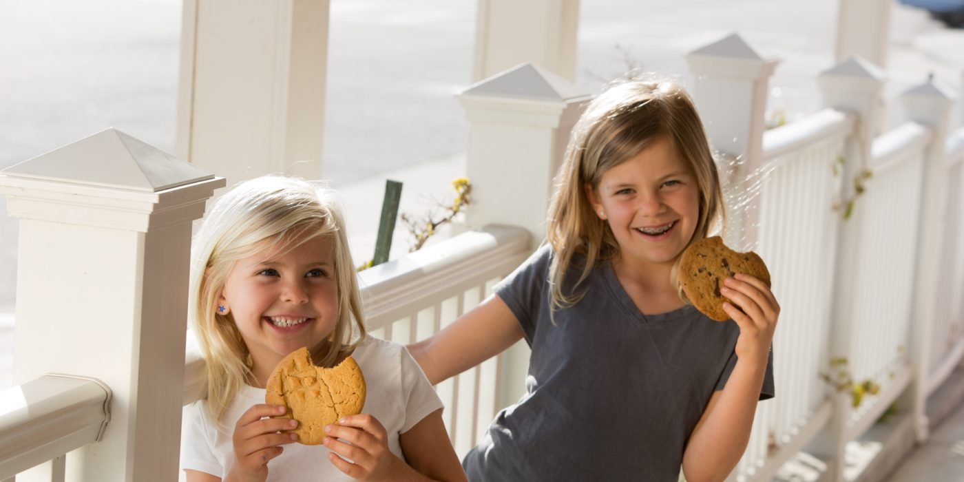 Girls enjoy cookies on balcony of Central California coast hotel on family vacation