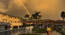 Rainbow arches over Pismo Lighthouse Suites on Cloudy Central Coast day