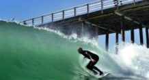 Surfer rides waves past Central California Beach Pier